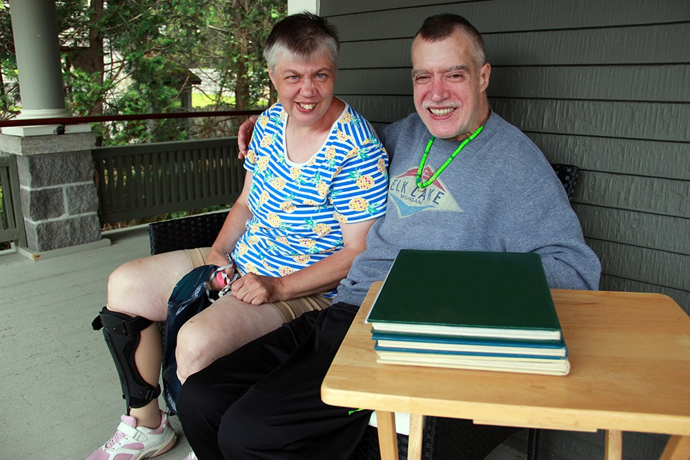 Janet and Chris Vance sitting on the porch of Chris' residence at Cook Street Community Home