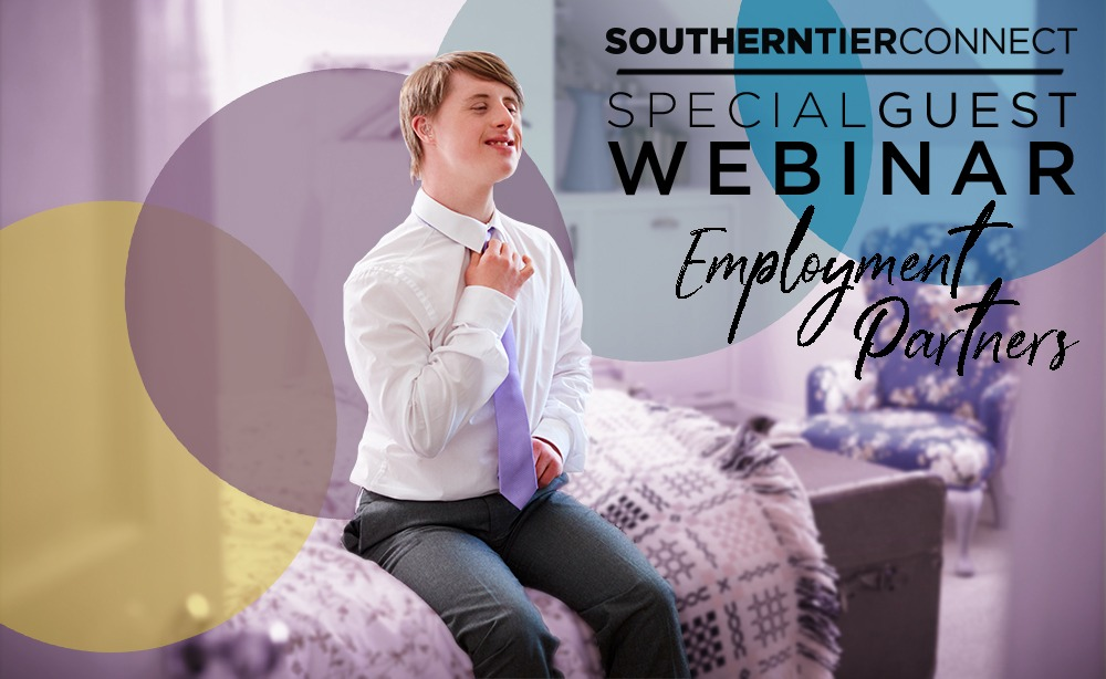 A young boy with down syndrome straightens his tie while sitting on a bed