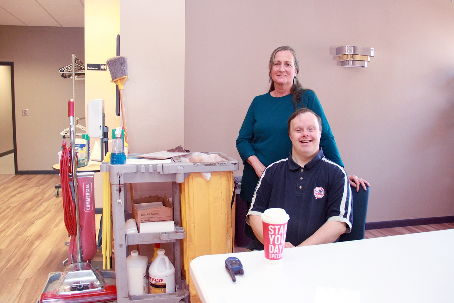 Care Coordination Manager Terri McCue poses with Jason LeBeau as he sits enjoying his extra-large decaf coffee before he starts his shift.