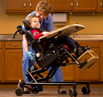 A child in an adaptive positioning chair with a therapist